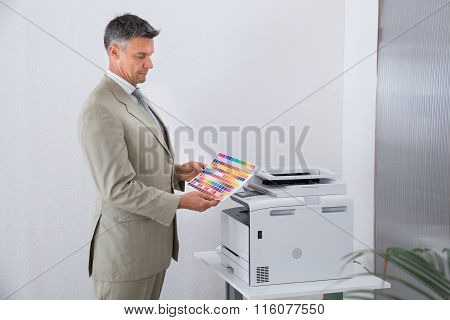 Businessman Looking At Multi Colored Paper By Color Printer