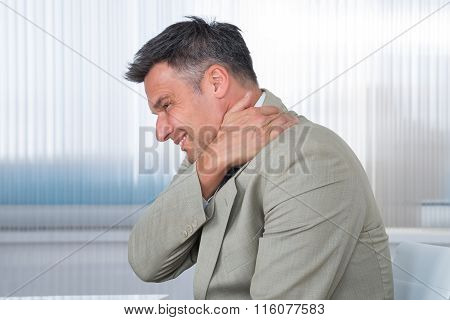 Businessman Suffering From Shoulder Pain In Office