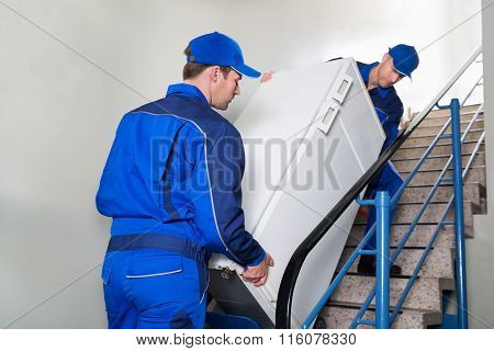 Movers Carrying Refrigerator On Steps