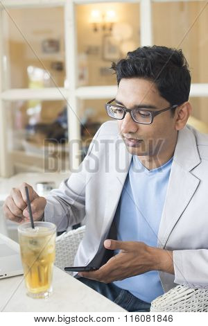 Indian Male Drinking With Laptop And Phone