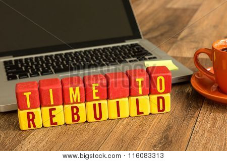 Time To Rebuild written on a wooden cube in a office desk
