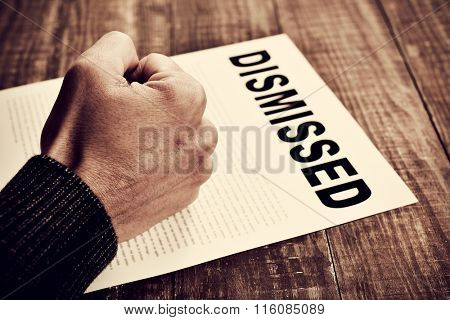 closeup of the fist of a young caucasian man on a document with the text dismissed, placed on a rustic wooden table