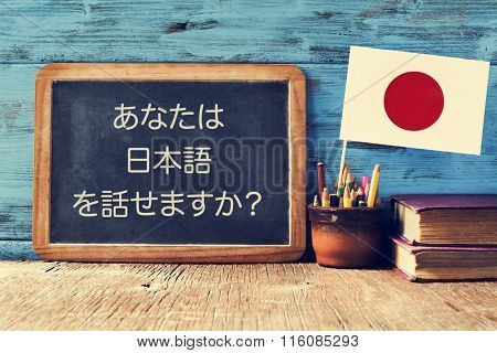 a chalkboard with the question do you speak Japanese? written in Japanese, a pot with pencils, some books and the flag of Japan, on a wooden desk