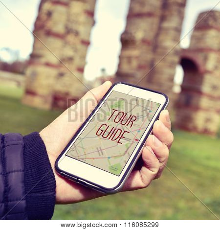 closeup of a young caucasian man with a smartphone with the text tour guide in its screen, in front of some ancient architectural remains