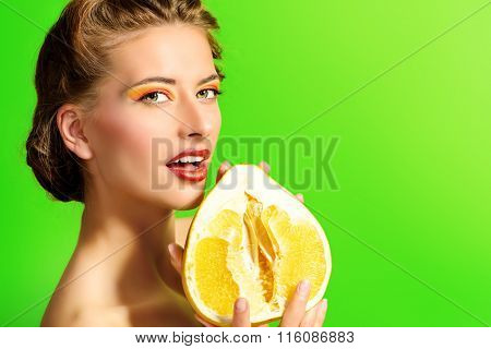 Fashionable young woman holding pomelo over green background. Tropical fruits.  Healthy eating. Beauty, cosmetics.