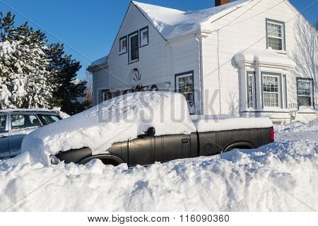 Piles of snow bury a truck and home in a North American suburb.