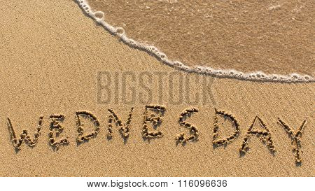 Inscription WEDNESDAY on a gentle beach sand with the soft wave (days of the week series)