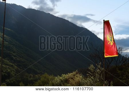 Montenegro flag next to the see and high mountains poster