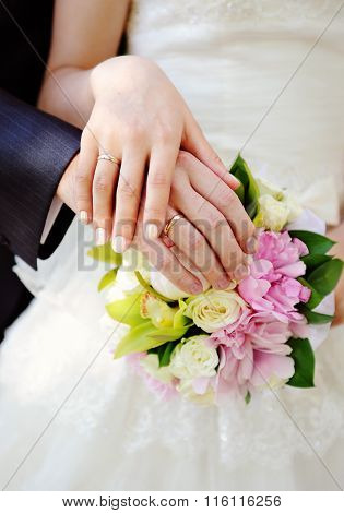 Hand Of The Groom And The Bride On Wedding Bouquet