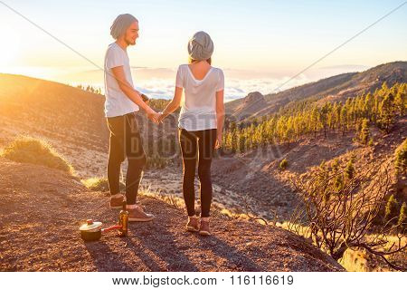 Young couple standing together on the beautiful landscape background