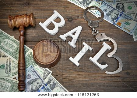 Gavel, Sign Bail, Handcuffs And Dollar Cash On Wood Background