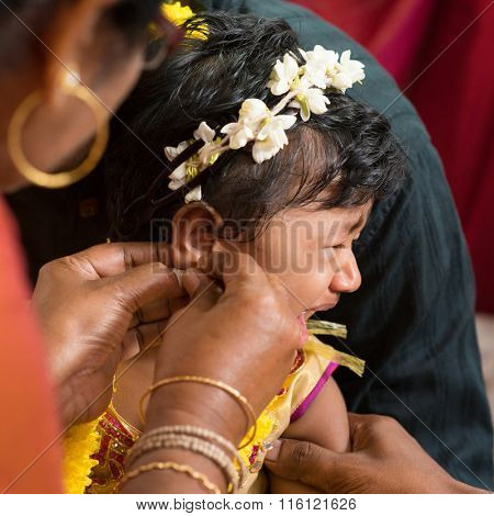 Traditional Indian Hindu family having ear piercing ceremony for baby girl in one year old.