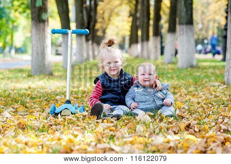 Young Kids Sit On Autumn Leafs