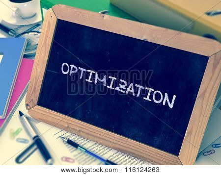Optimization Handwritten by White Chalk on a Blackboard. Composition with Small Chalkboard on Background of Working Table with Office Folders, Stationery, Reports. Blurred Background. Toned Image. poster
