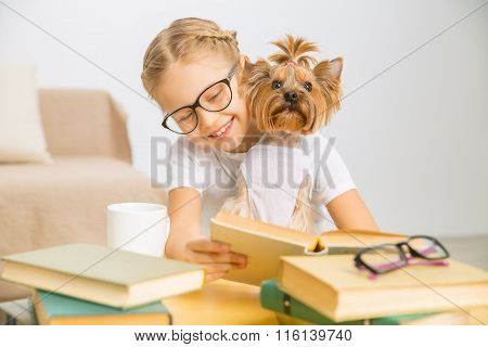 Little girl is reading with her dog.