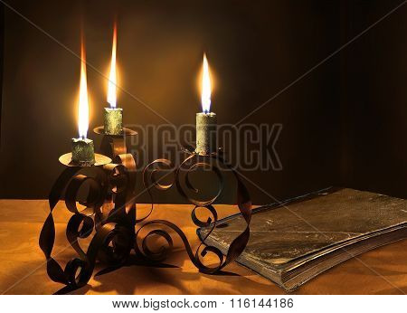 Closed Old Book And Three Burning Candles In The Candlestick