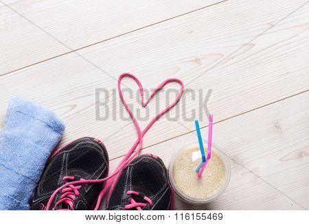 Sport concept healthy lifestyle. Female sportshoes towel and smoothie in the cup on the floor ready for jogging. Top view poster
