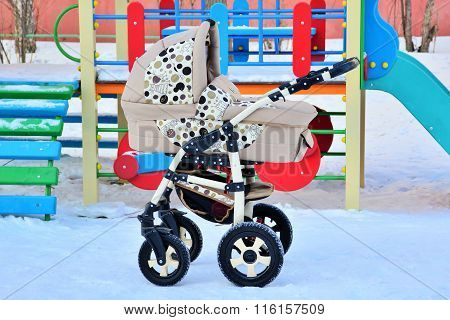 Beige baby stroller at the playground in winter
