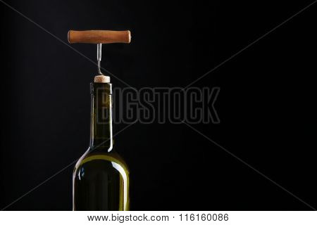 Corkscrew and wine bottle on a black background