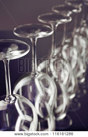 Wine glasses in a row upside down on light grey background