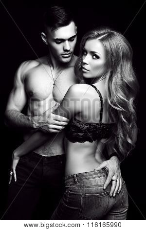 fashion black and white studio photo of beautiful couple with sportive sexy bodies gorgeous woman with long blond hair embracing handsome brunette man poster