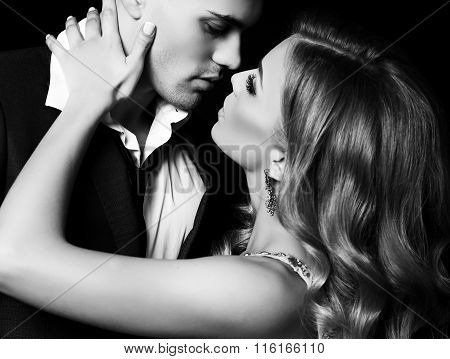 fashion black and white studio photo of beautiful couple in elegant clothes gorgeous woman with long blond hair embracing handsome brunette man poster