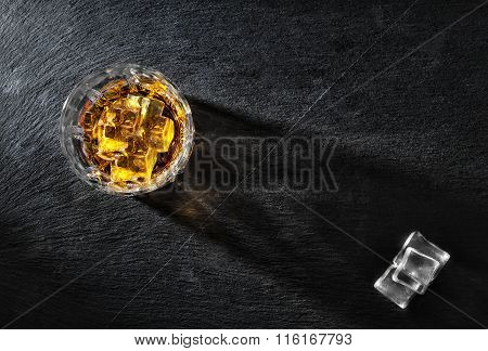 Glass of whiskey with ice on black textural background