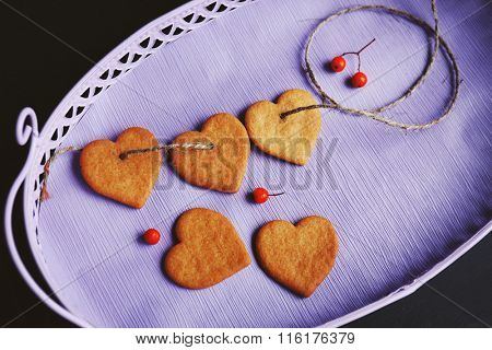 Heart shaped biscuits with ash berries on a lilac tray, top view