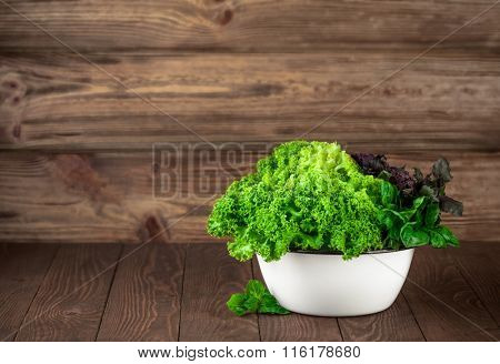 Fresh leaves lettuce and basil in dish on wooden board. Stock photo. Stock photo