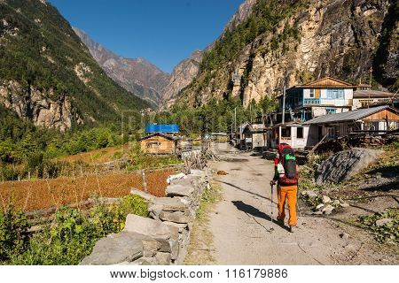 Hiker passing a village.