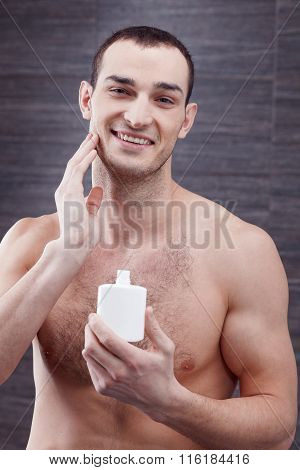 Attractive young man is using moisturizer after shaving