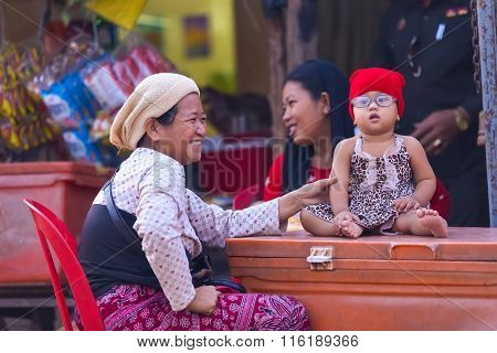 Little Girl With Glasses Presumably With Down Syndrome Is Enjoying Being With Her Mother And Grandmo