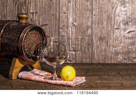 Barrel With Lemon And An Empty Brandy Glass On An Old Table