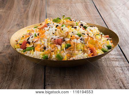 Veg biryani or veg pulav served in a round brass bowl over wooden background