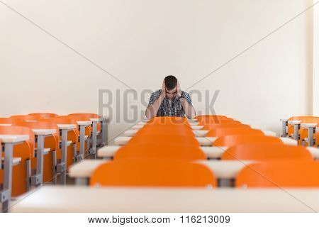 Student With Books Sitting In Classroom
