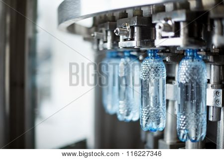 Plastic Water Bottles On Conveyor And Water Bottling Machine Industry. Water Bottling Plant.