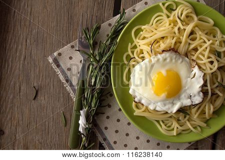 Spaghetti With Fried Egg And Rosemary On Green Plate