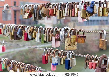 Love Padlocks Hanging From Railing On Bridge