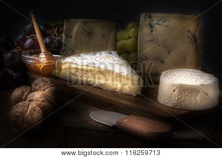 Wooden Board With Cheeses, Grapes, Nuts And Honey
