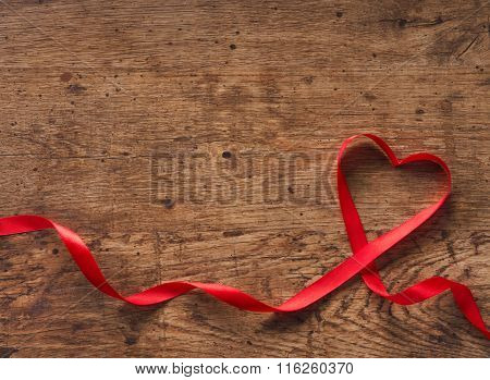 Red Ribbon Heart on a wooden background.