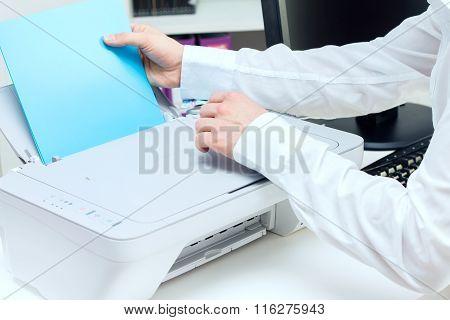 Man puts stack of paper to printer