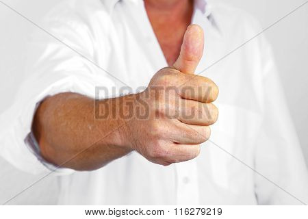 handsome man in white business shirt shows thumbs up sign