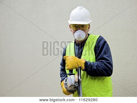 Construction worker in safety gear with angle grinder