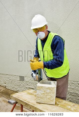 Construction worker wears dust mask while cutting cement block