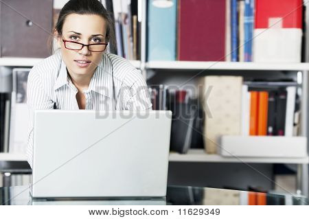 Young women with laptop is near bookshelf