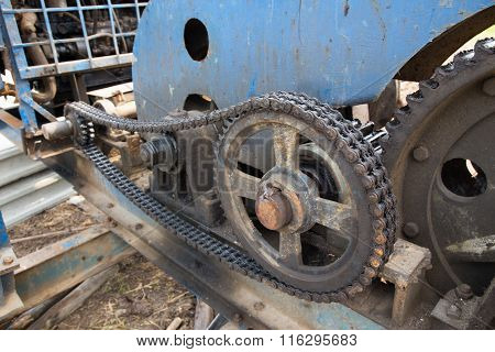 dirty chain and cogwheel of pile driver at construction site