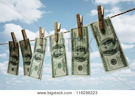 Hundred dollar bills hanging from a clothesline concept for money laundering, investment or venture capital funding