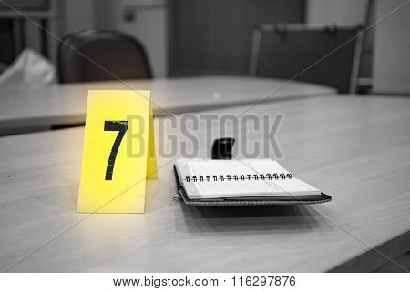 Yellow Evidence Number Pad And Evidence On Table In Crime Scene