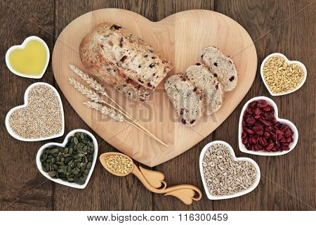 Cranberry and seed bread loaf on a heart shaped wooden board with wheat sheaths, love spoon with grain, pumpkin and sunflower seeds, cranberries, oatmeal and olive oil on old oak background.