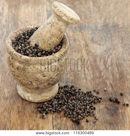 Vitex agnus castus herb used in natural alternative herbal medicine in a mortar with pestle over old wood background. Used as an aphrodisiac and tonic for male female reproductive systems.